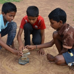 Boys pile rocks for game outside